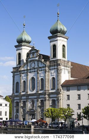 LUCERNE SWITZERLAND - MAY 04 2016: The front facade of the Jesuit church at the bank of the river Reuss in the old town. It is one of the most visited tourist attractions in the city