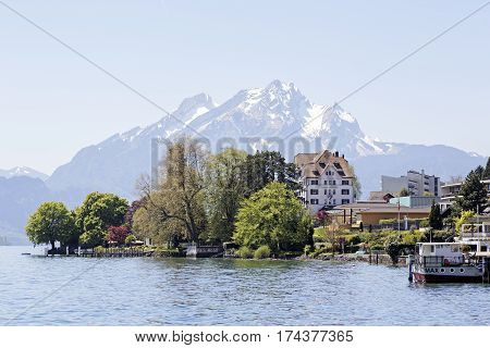 WEGGIS SWITZERLAND - MAY 05 2016: Trees and buildings on the shore of Lake Lucerne and in the distance the snow-capped Mount Pilatus. The scenic area is a popular destination for tourist trips