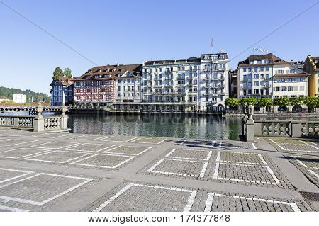 LUCERNE SWITZERLAND - MAY 05 2016: Square that is fenced by stone balustrade and it is covered with cobblestones. There are historical buildings on the other side of the river Reuss