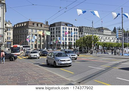 LUCERNE SWITZERLAND - MAY 05 2016: Traffic in the city. Many cars on the street pedestrians on sidewalks and a few massive townhouses creates cityscape of this city