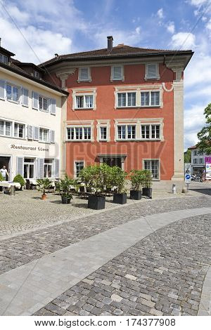 RAPPERSWIL SWITZERLAND - MAY 10 2016: Two buildings on a side street. On the sidewalk in front of those houses restaurant has placed its outdoor seating area.