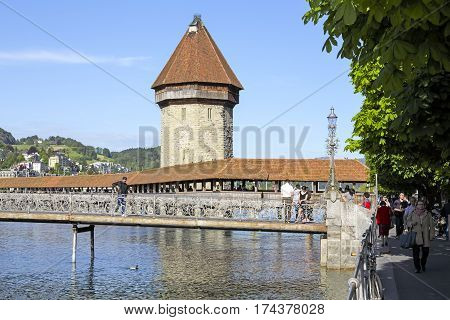 LUCERNE SWITZERLAND - MAY 09 2016: Two of most recognizable landmarks in the city are the octagonal tower and roofed Chapel Bridge by the river Reuss
