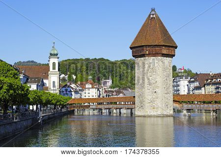 LUCERNE SWITZERLAND - MAY 05 2016: Octagonal tower and the Roofed Chapel Bridge together with the Jesuit Church these are most recognizable landmarks in the city and are located by the river Reuss