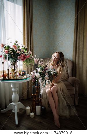 Beautiful Young Woman In A House Dress In The Boudoir, Decorated With Beautiful Flowers, Sitting On