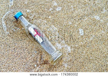 Bottle with message on sandy beach, horizontal image