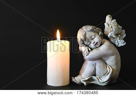 Candle and angel figurine on black background