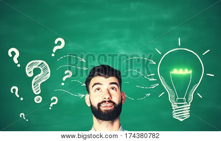 Cheerful man with drawn question marks and lamp on chalkboard background. Idea concept