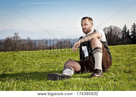 A traditional bavarian man in front of the German Alps