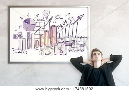 Relaxing european man on concrete background with business sketch in frame. Profit concept