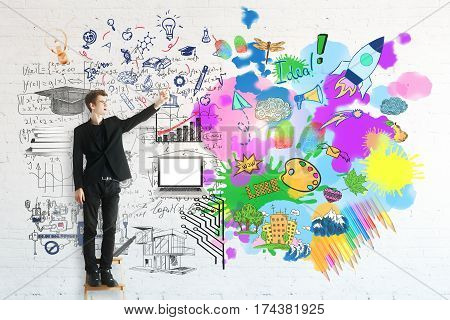 Creative and analytical thinking concept. Young businessman pointing at colorful sketch and mathematical formulas on brick background