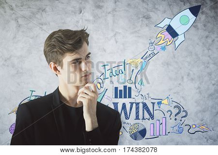Handsome caucasian man thinking on textured concrete background with rocket ship sketch. Young entrepreneur concept