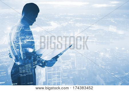 Side view of young businessman analyzing contract on abstract city background with copy space. Double exposure. Work concept