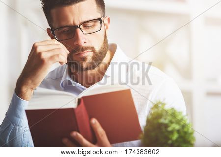 Close up portrait of attractive european man reading book at modern workplace with decorative plant and other items. Education concept