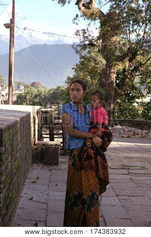 POKHARA, NEPAL. 25 September 2008:  Young woman - Hindu pilgrim with a little child at a Hindu temple of goddess Durga. Himalayas, Pokhara, Nepal.