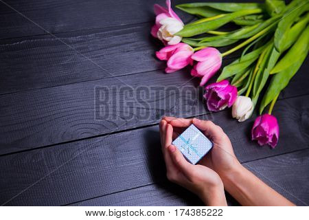 Bouquet Of Tender Pink Tulips With Gift Box On Black Wooden Background
