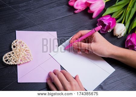 Female Hands Writing On Clear Paper With Wicker Heart And Bouquet Of Tulips
