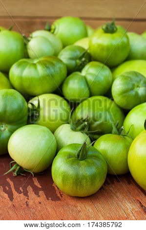 Green Tomatoes On Wooden Brown Board Close Up.