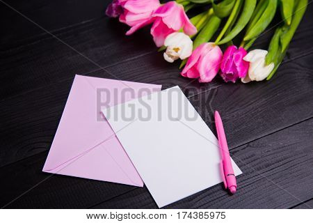 Bouquet Of Tender Pink Tulips And Clear Paper On Black Wooden Background