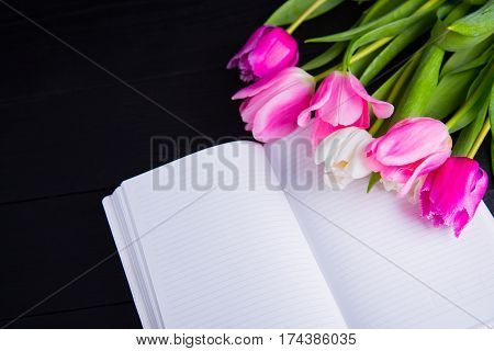 Bouquet Of Tender Pink Tulips And Open Notebook On Black Wooden Background