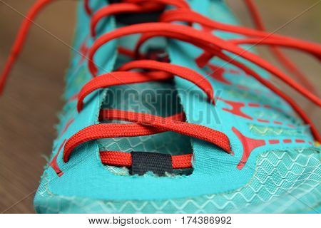 close-up shot of a red lace, blue shoe
