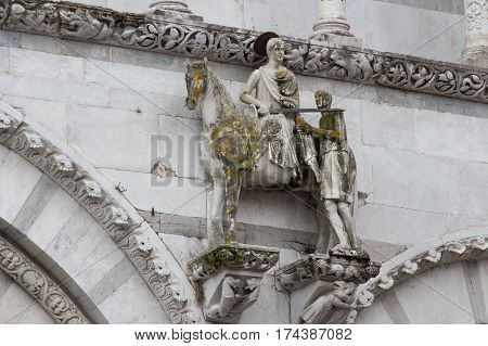 Italy Lucca - September 18 2016: the view of the statue of Saint Martin shares his cloak with a beggar. Lucca Cathedral. Cattedrale di San Martino on September 18 2016 in Lucca Tuscany Italy.