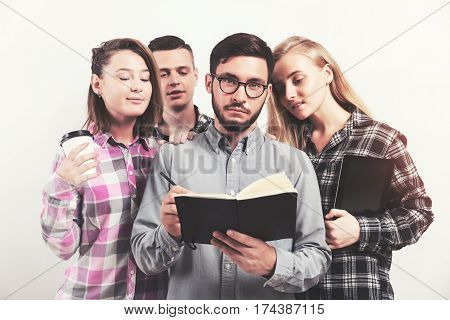 Group of students standing close to each other. One is reading a book. The rest are looking over his shoulder. Toned image. Sunlight