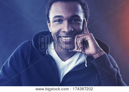 Close up portrait of a cheerful African American young man wearing a white T-shirt and a black hoodie and smiling. Toned image.