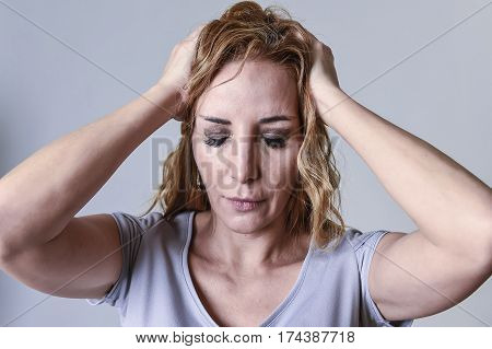 blond attractive woman on her thirties sad and depressed looking desperate in sorrow and grief facial expression in female depression emotion concept isolated on grey background