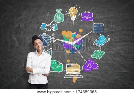 Portrait of an African American woman standing near a blackboard with a business clock on it. Concept of time management.