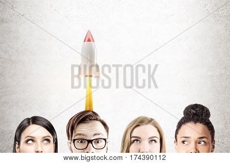 Close up of heads of a business team members against a concrete wall. There is a rocket launching behind them. Mock up.