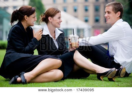 Three young professionals sitting outside in park having coffee break