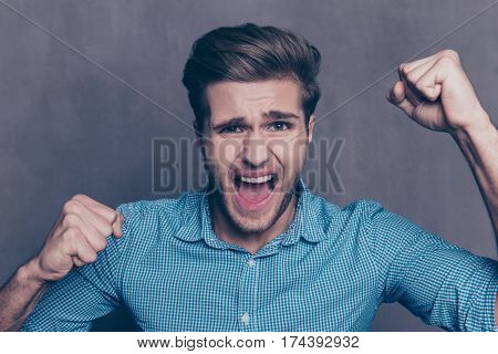 A Young Man Triumphing And Raising His Fists On Isolated Background