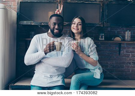 Two Cheerful Mixed Race People Drinking Coffee In Kitchen