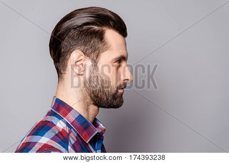 A profile portrait of a young handsome man with trendy stylish hairdo against gray background poster