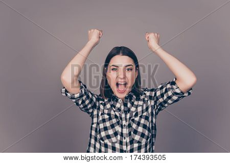 Excited Young Woman Triumphing With Raised Hands Isolated On Gray Background