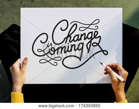 Hand Holding Pen Paper Writing Change is Coming Board