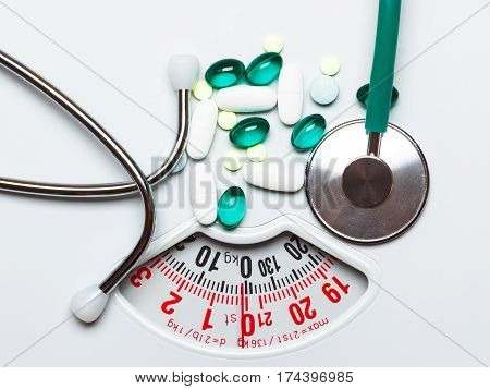 Healthy eating medicine health care food supplements and weight loss concept. Pills with stethoscope on white scales