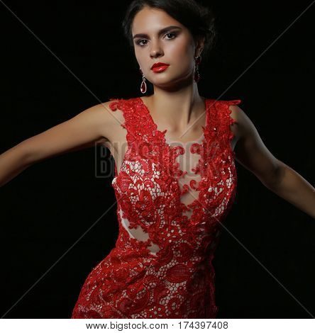 Young beauty woman in red dress. Isolated on black