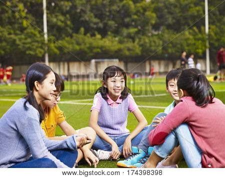 group of asian elementary school boys and girls sitting and chatting on playground grass