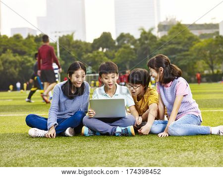 group of asian elementary school children sitting on playground grass looking at laptop computer