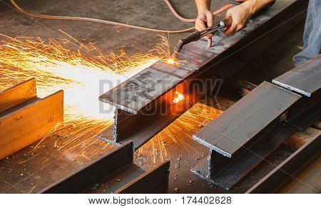 Worker cutting steel beam using metal torch in manufacturing factory.