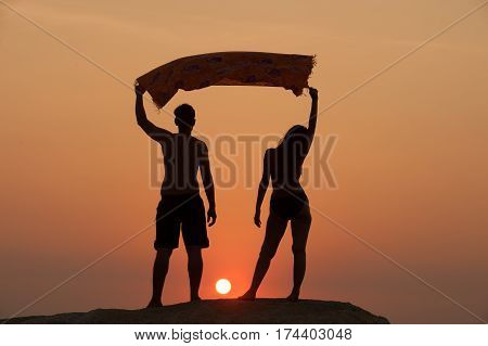 Positive couple holding fabric up and expressing gladness while standing on stone in Sunset.