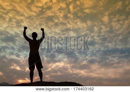 Positive male holding hand up and expressing gladness while standing on stone in Sunset.