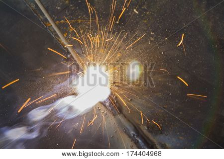 Metal Welding with sparks, Shielded metal arc welding (SMAW) process.