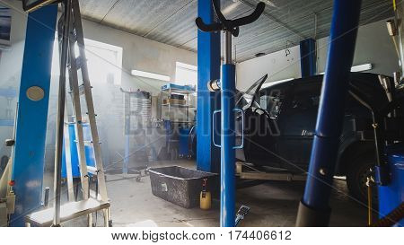 View of car service station - dust particles float in the air at sunny midday, horizontal