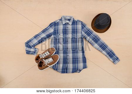 Man's cotton blue plaid shirt ,hat,on wooden background