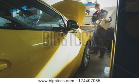 Car mechanic blows air filter of automobile in service, wide angle, horizontal