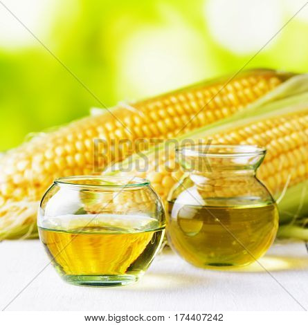 Corn Oil And Corn Cobs On A Garden Table