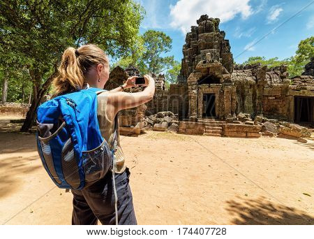 Tourist Photographing The Ancient Gopura In Angkor, Cambodia