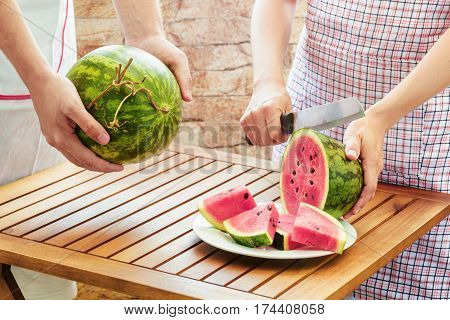 Young Woman In Apron Slicing Fresh Ripe Watermelon